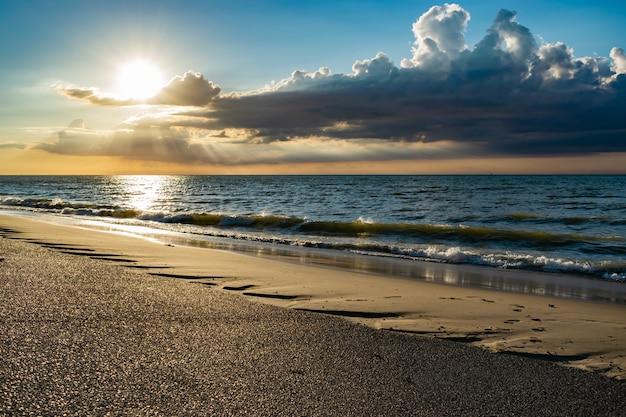 Por do sol pitoresco no mar com raios de sol e as nuvens escuras acima do mar do norte.