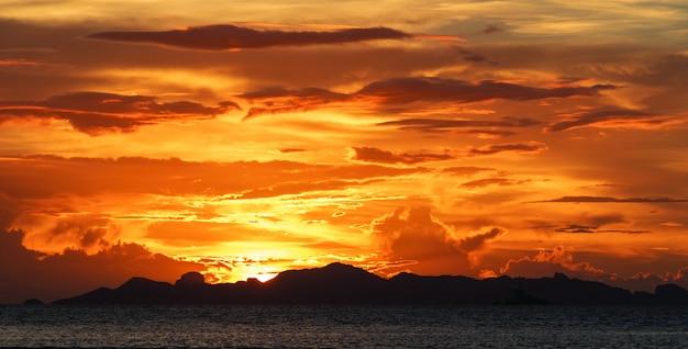 Pôr do sol praia linda com grandes nuvens e fundo do céu de luz dourada