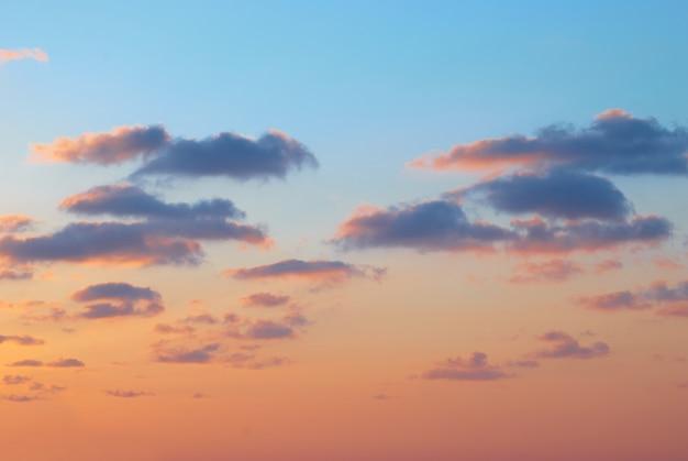 Pôr do sol romântico com lindas nuvens azuis, vermelhas e amarelas.