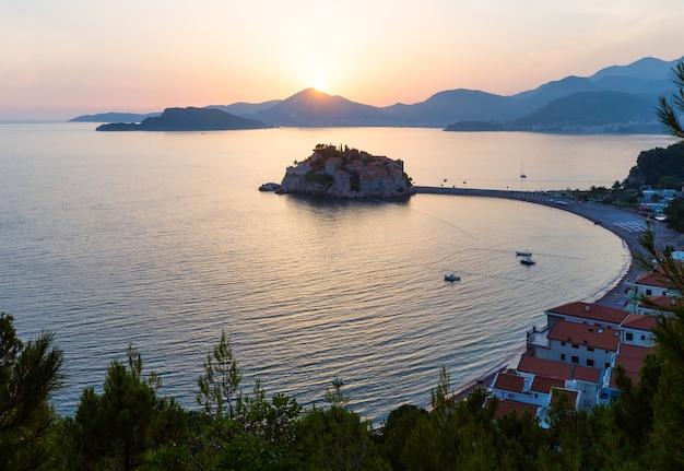 Pôr do sol rosa e vista da ilhota do mar sveti stefan de cima (montenegro, 6 quilômetros a sudeste de budva)