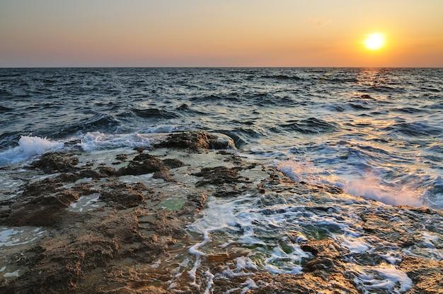 Pôr do sol rosa lindo e pedras de água ao longo da costa rochosa do mar negro, na crimeia, num dia de verão.
