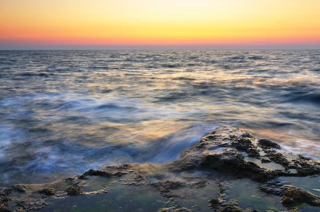 Pôr do sol rosa lindo e pedras de água com musgo verde