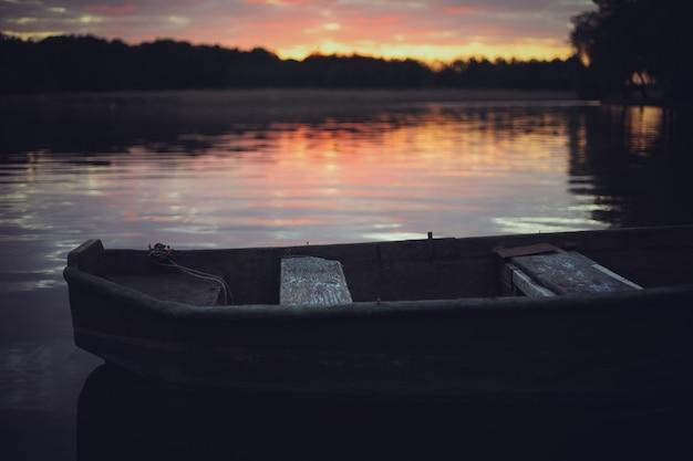 Pôr do sol rosa no lago com um velho barco. fundo desfocado natural, céu pôr do sol sobre o lago. silhueta da natureza