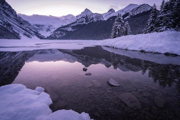 Pôr do sol roxo de inverno na margem de um lago parcialmente congelado, em lake louise, alberta, canadá