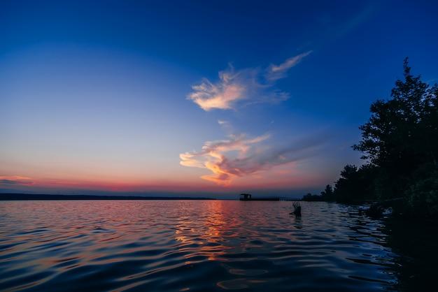 Pôr do sol sobre a água com um cais na noite de verão no mar com um fundo azul vermelho
