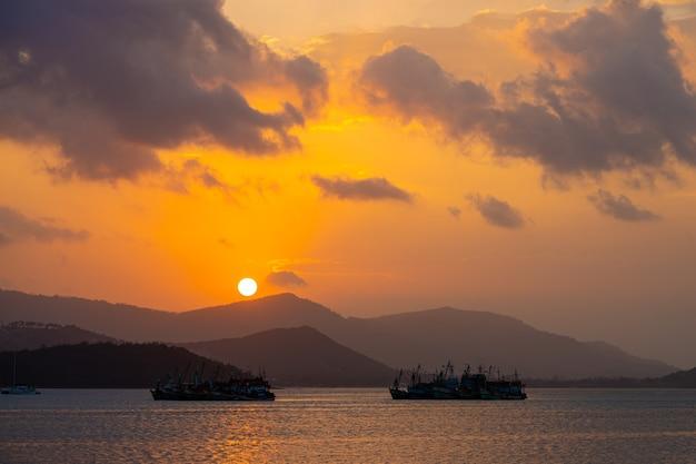 Pôr do sol sobre a baía com barcos de pesca.