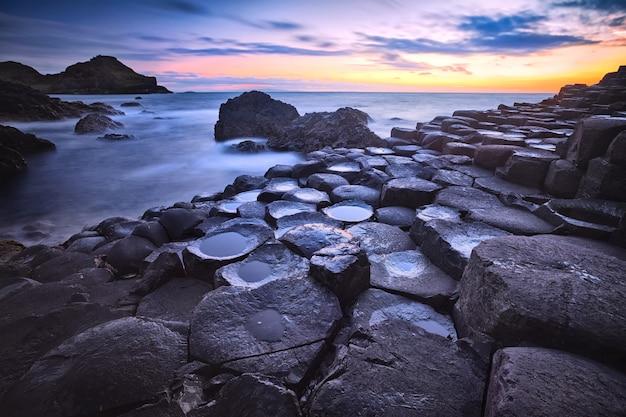 Pôr do sol sobre a formação de rochas calçada de gigantes, condado de antrim, irlanda do norte, reino unido