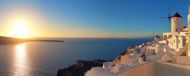 Pôr do sol sobre a ilha de santorini, na grécia. igreja tradicional, apartamentos e moinhos de vento na vila de oia.