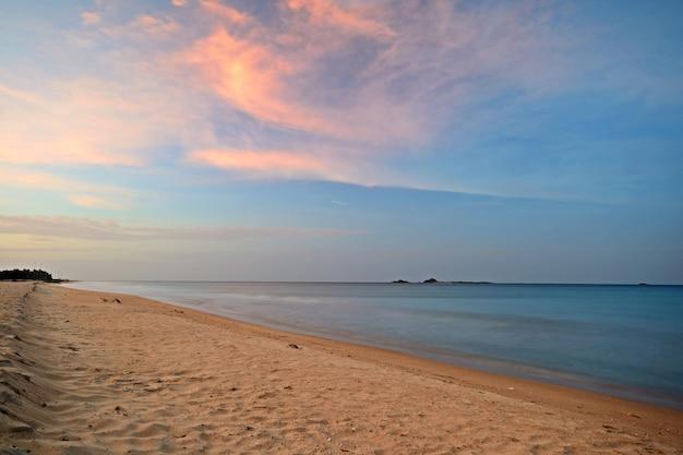 Pôr do sol sobre a praia deserta em nilaveli, sri lanka