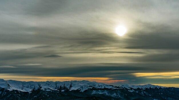 Pôr do sol sobre as montanhas do cáucaso cobertas pela neve na estância de esqui de krasnaya polyana, na rússia.