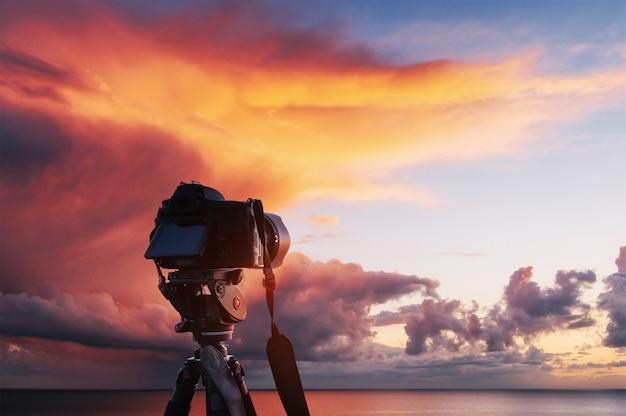 Pôr do sol sobre o mar, a costa. bola de fogo ocidental do sol acima do horizonte em um céu laranja colorido.