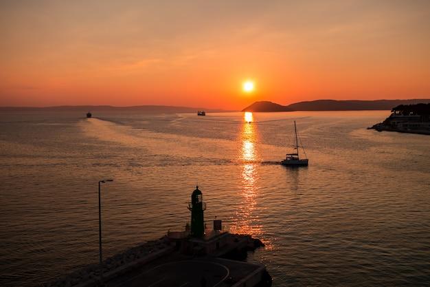 Pôr do sol sobre o mar adriático e seus barcos brincando nas reflexões na entrada do porto de split, na croácia.