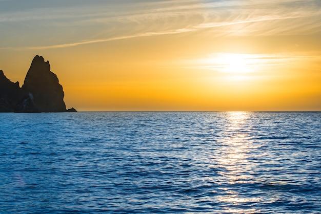 Pôr do sol sobre o mar azul com pedras e céu laranja