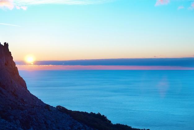 Pôr do sol sobre o mar com sol, céu azul, nuvens e montanha