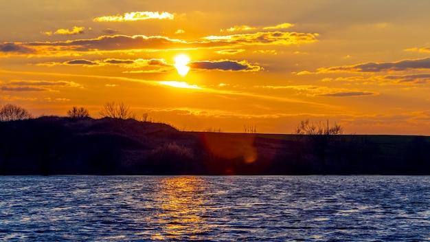 Pôr do sol sobre o rio, ondas na água e reflexo do sol