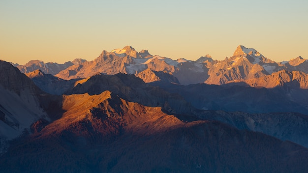 Pôr do sol sobre os alpes. céu colorido, picos de montanha da alta altitude com geleiras, parque nacional do des ecrins de massif, frança.