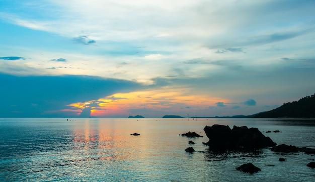 Pôr do sol tranquilo refletido no mar calmo com silhuetas de rochas em koh pha ngan tailândia