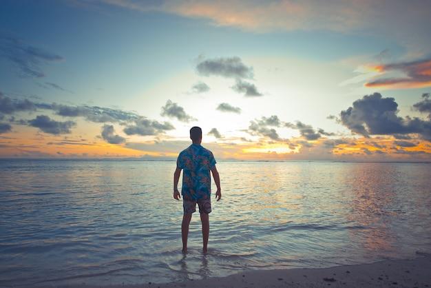 Pôr do sol tropical em frente ao oceano em uma bela ilha. homem de férias, aproveitando o momento