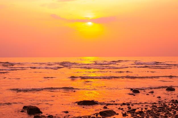 Pôr do sol vermelho-amarelado no mar no verão, na costa