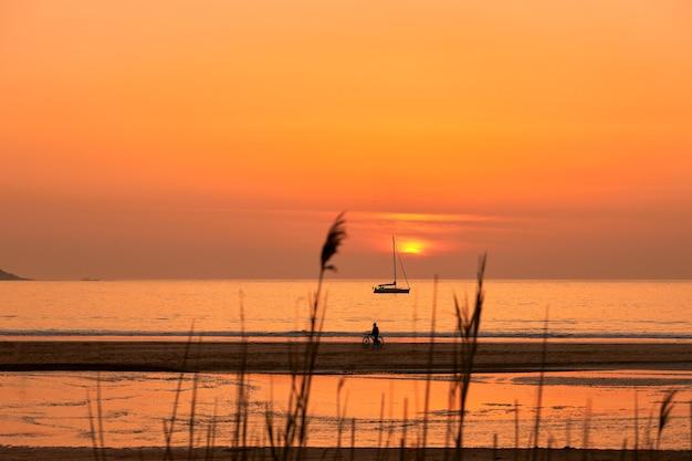 Pôr do sol vermelho com pessoas passeando na praia de playa america, na galiza, espanha.