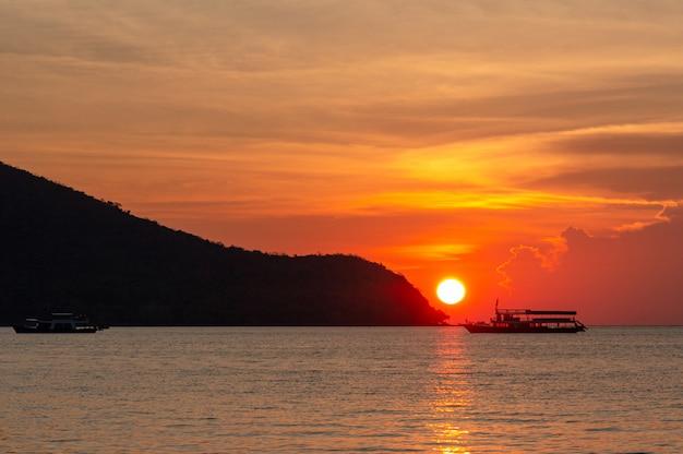 Por do sol vermelho do céu no oceano com uma silhueta do barco. nuvens acima e oceano em primeiro plano.