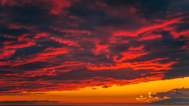 Pôr do sol vermelho-sangue brilhante nas montanhas acima do mar