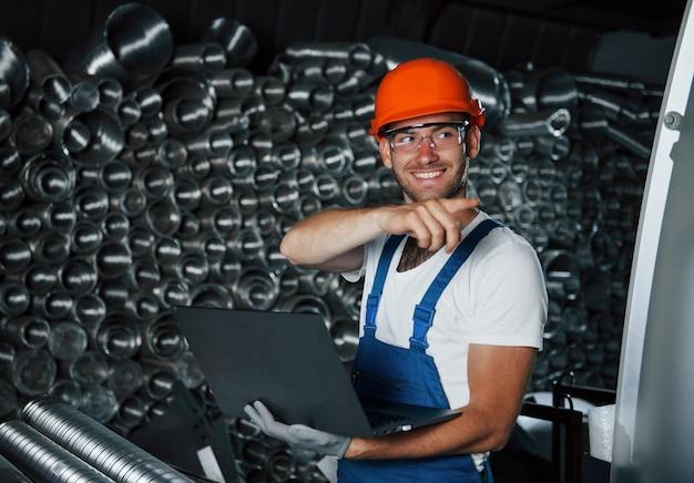 Por esse lado. homem de uniforme trabalha na produção. tecnologia industrial moderna.