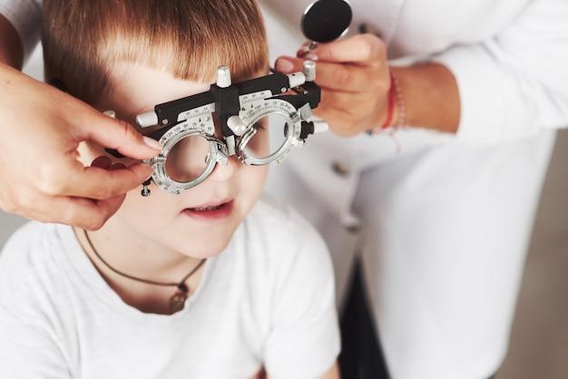 Por favor, espere por mim ajustar o dispositivo. criança sentada no gabinete do médico e testou sua acuidade visual.