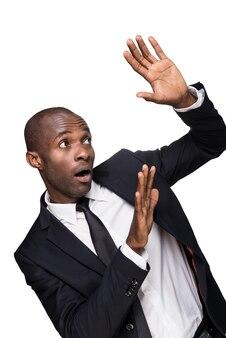Por favor não! jovem africano apavorado em trajes formais, olhando para cima e gesticulando em pé, isolado no fundo branco