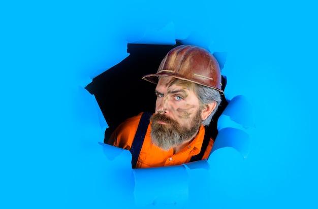 Por meio de um retrato publicitário em papel de um reparador engraçado, um reparador, de ferramentas de reparo de capacetes