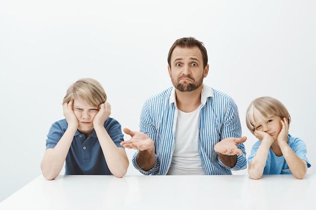 Por que os filhos estão loucos. retrato do sogro nervoso sem noção sentado com dois meninos bonitos à mesa