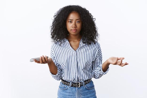 Por que. retrato confuso questionou mulher bonita de pele escura e cabelos cacheados usando blusa encolhendo os ombros com as mãos para o lado consternada segurando smartphone não consigo entender, sem noção do que aconteceu