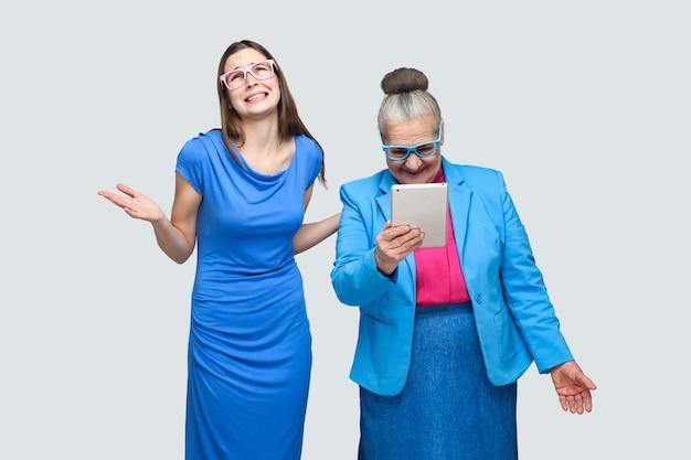 Por que você fez isso? mulher infeliz neta em pé perto de mulher envelhecida olhar no tablet. relacionamento na família. neta com a avó. interno, foto de estúdio, isolado em fundo cinza