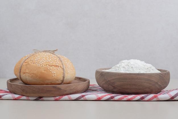 Pôr um pão de hambúrguer na corda com farinha na placa de madeira. foto de alta qualidade