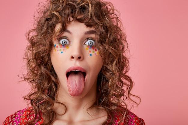 Poratrait de uma jovem mulher encaracolada de olhos azuis com pontos multicoloridos no rosto olhando com olhos arregalados e mostrando a língua, isolada