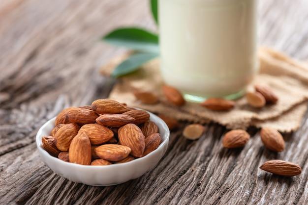 Porca das amêndoas, alimento seco da nutrição do petisco com a garrafa do leite da amêndoa no fundo de madeira.