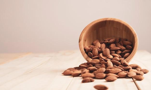 Porca de amêndoas em uma tigela de madeira e despeje na mesa com espaço de cópia. a noz de amêndoa é um alimento de dieta saudável com alto teor de proteína, baixo teor de gordura e aminoácidos essenciais.