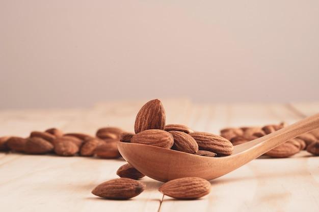 Porca de amêndoas na colher de pau e despeje na mesa com espaço de cópia. a noz de amêndoa é um alimento de dieta saudável com alto teor de proteína, baixo teor de gordura e aminoácidos essenciais.