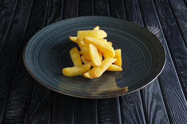 Porção de batata frita na mesa de madeira escura