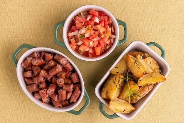Porção de batatas assadas, linguiça e vinagrete