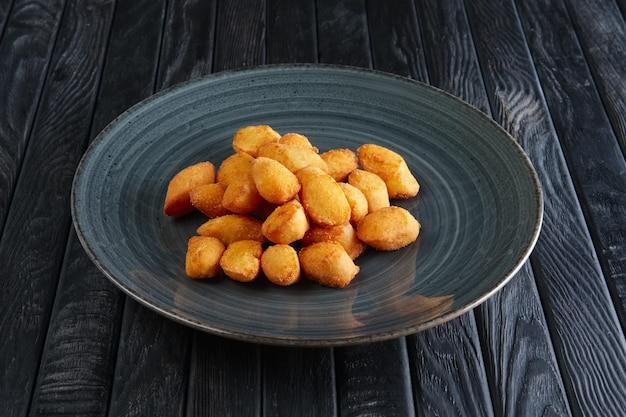 Porção de bolas de batata frita na mesa de madeira escura