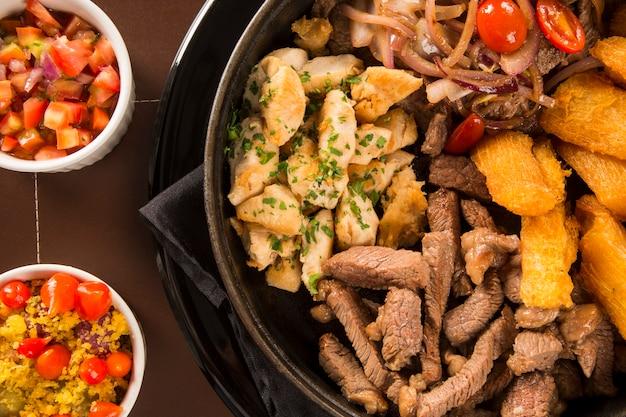 Porção de carne com batata frita e mandioca frita, cebola com legumes e pimentão