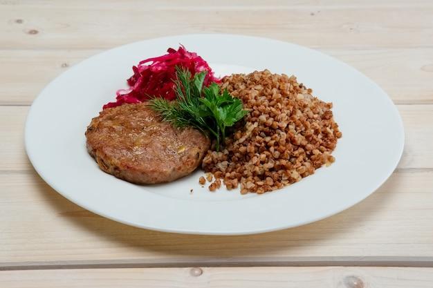 Porção de costeleta de vaca frita, trigo cozido e repolho roxo em conserva