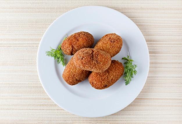 Porção de croquetes fritos recheados em um prato