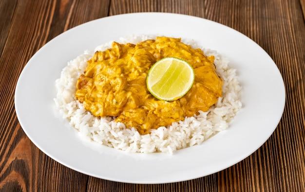 Porção de curry de frango guarnecido com arroz e limão fresco