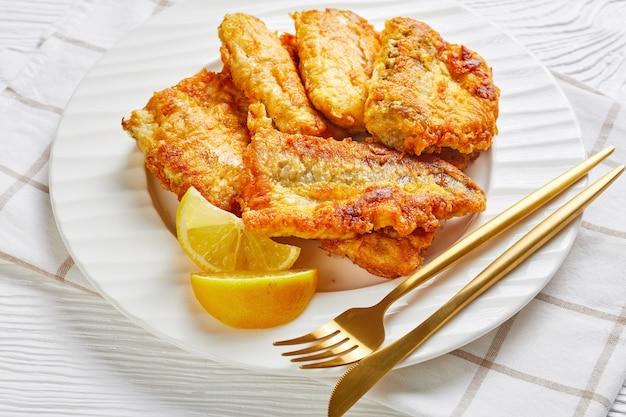 Porção de filé de pescada frito e maltratado, servido em prato branco com fatias de limão, talheres dourados sobre superfície de madeira branca com guardanapo, close-up