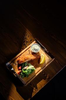 Porção de filé de salmão com ervas sobre uma mesa de madeira. vista do topo