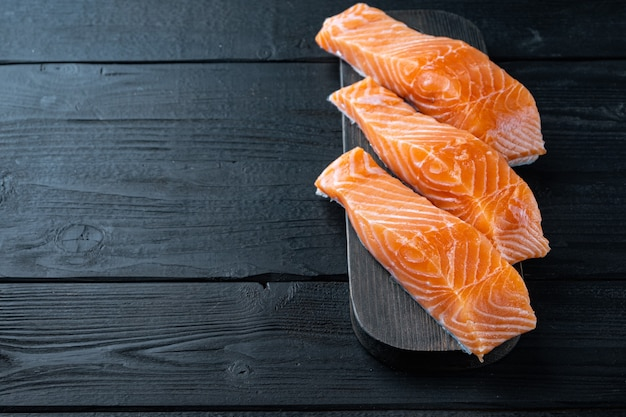Porção de filé de salmão na mesa de madeira preta