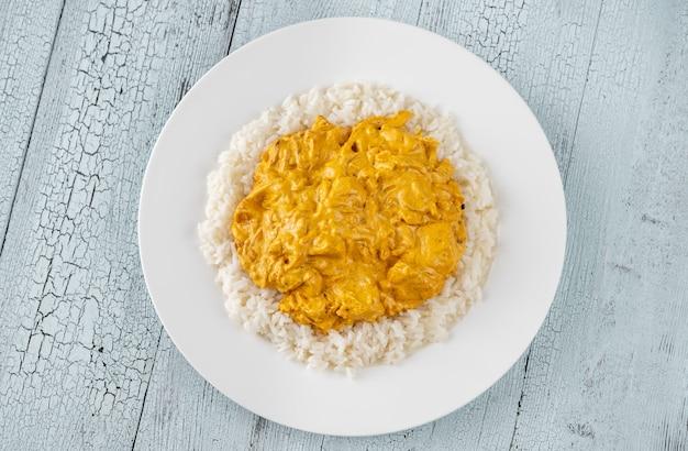 Porção de frango ao curry guarnecido com arroz