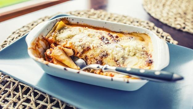 Porção de lasagme à bolonhesa no prato na mesa no restaurante.
